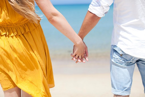 外国人カップル 人物 2人 男性 女性 男女 自然 風景 リゾート アウトドア 海 空 風 青空 青 白 波 海辺 海岸 砂 砂浜 ビーチ 水平線 金髪 ロングヘア ウエーブ  シャツ 腕まくり 黄色 山吹色 デート 休日 旅行 幸せ 幸福  楽しい ハッピー 手 手をつなぐ 手を握る 立つ 後ろ姿 ズーム クローズアップ 海外 外国