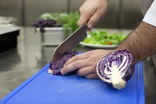 厨房 台所 キッチン 料理 調理  コック シェフ 料理人 包丁 ナイフ 切る カット まな板 レストラン 仕込み 下準備 野菜 青 バット ボディパーツ 腕 持つ 手 紫キャベツ レッドキャベツ 赤きゃべつ 手元 アップ 男性 外国人