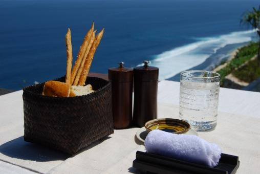 海 レストラン テラス パン 水 グラス かご おしぼり 塩 胡椒 オリーブオイル アジア 快晴 風景 バリ 高台 リゾート 食事
