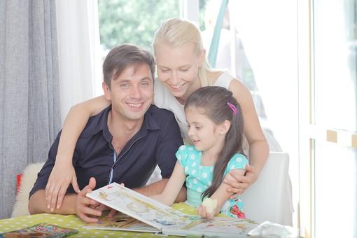 人物写真 ポートレート ポートレイト 人物 人 人間 外国人 幼児 子供  女子 女の子 女児 テーブル 室内 屋内 親子  キッチン 台所 男性 父親 読む 絵本 読書 読み聞かせ 水玉模様 笑顔 笑み 女性 母親 肩を抱く 家族 mdff013 mdfm005 mdfk001