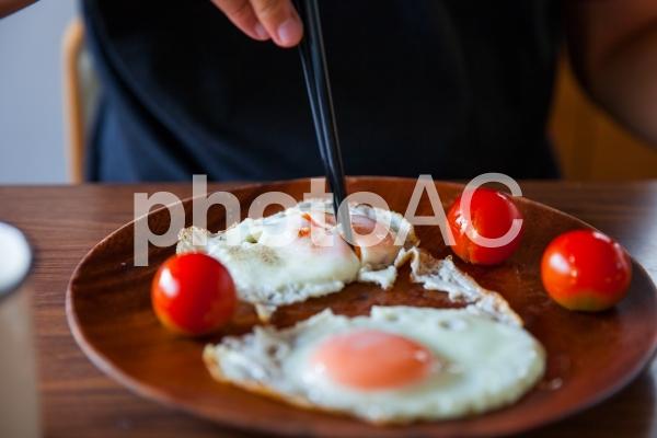 目玉焼きを食べる人の写真