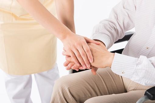老人 高齢者 お年寄り シニア 手 両手 介護士 看護師 エプロン 支える 添える アップ  介護 不自由 椅子 ヘルパー 白バック 白背景 車いす 車椅子 白 シャツ 座る ベージュ 茶色 握る アップ