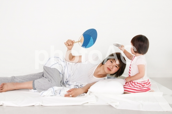 夏バテ・熱中症の女性と介抱する子供の写真