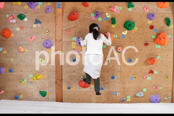 ボルダリングに挑戦する女の子の写真
