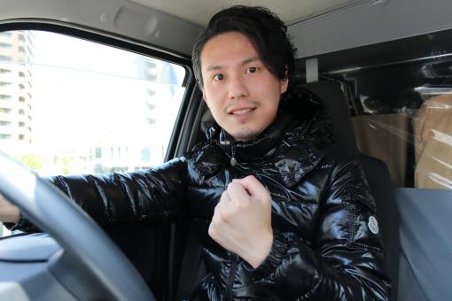 車内でガッツポーズする男性の写真