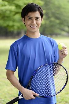 全身 人物 人 男性 男 大人 日本人 20代 屋外 公園  スポーツ 運動 Tシャツ 青 球技 テニス 趣味 ラケット ボール インストラクター コーチ トレーナー 選手 立つ 爽やか 笑顔 若い 健康管理 体調維持 ライフスタイル レジャー カメラ目線 mdjm025