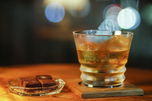 飲み物 飲料 ドリンク アルコール 酒 洋酒 液体 氷 冷たい ウイスキー グラス ガラス コップ 透明 コースター テーブル 机 夜 明かり 光 綺麗 ネオン イルミネーション 輝く ムード バー 室内 屋内 無人 食べ物 おつまみ 肴 酒肴品 チョコレート 小皿