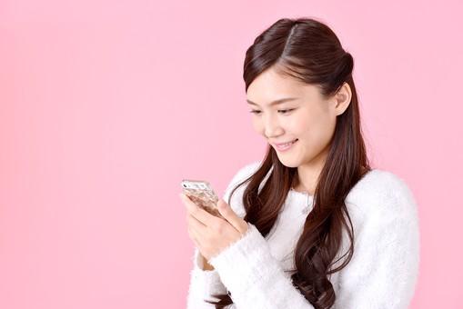 人物 女性 日本人 若者 若い 20代 美人 かわいい ロングヘア カジュアル ラフ 私服 セーター ニット 屋内 スタジオ撮影 背景 ピンク ピンクバック ポーズ おすすめ 上半身 スマホ スマートフォン 携帯 電話 通話 話す 笑顔 mdjf007