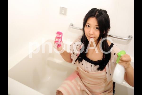 風呂掃除をするエプロン姿の女性の写真