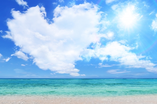 夏の太陽光とハート型の雲と青空と海と白い砂浜の写真