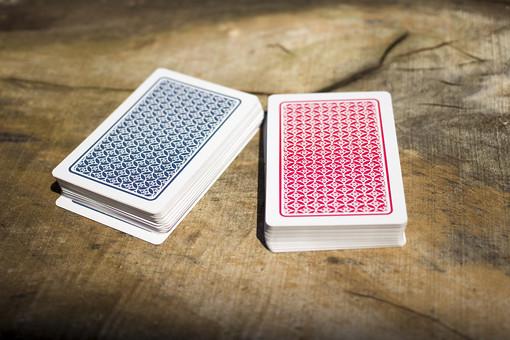 トランプ カード ゲーム 札 娯楽 木 屋外 茶色 机 置く テーブル 青 赤 裏  絵札  木目 手品 マジック 遊び  重ねる 配る 切る カードゲーム 束 裏側