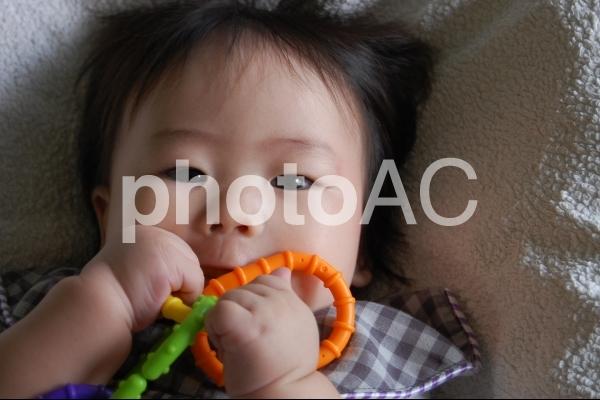 おもちゃを口に含む赤ちゃんの写真