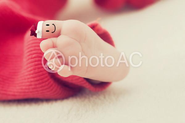 サンタ帽をかぶってニッコリ笑う赤ちゃんの足の親指の写真