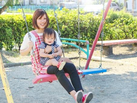 子供とブランコで遊ぶエプロン姿の女性の写真