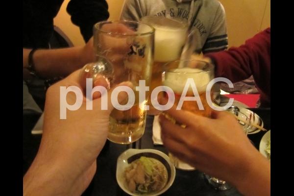 友達と居酒屋でビールジョッキで乾杯の写真