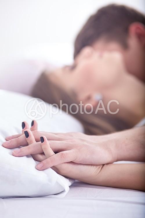 手を重ねるベッドの中のカップル25の写真