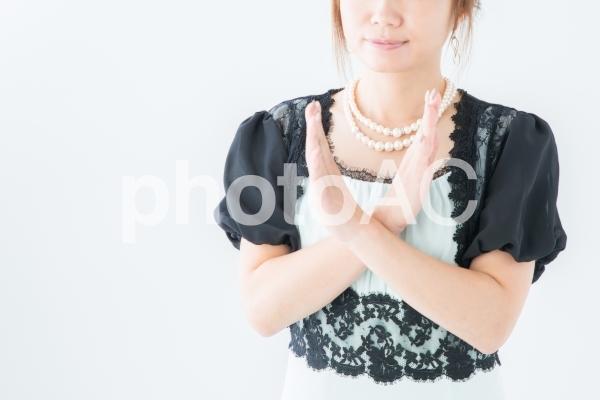 バツサインするドレス姿の女性の写真