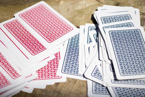 トランプ カード ゲーム 札 娯楽 木 屋外 茶色 机 テーブル  絵札 黒 木目 手品 マジック 遊び 絵札  並べる 裏 裏側 赤 青 乱雑  重ねる 配る 切る カードゲーム