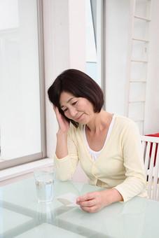 シニア 老人 おばあちゃん おばあさん 女性 中年 病気 熱 発熱 つらい 風邪 かぜ 疲れ だるい 薬 くすり 粉薬 水 人物 日本人 60代 頭痛 体調不良 テーブル 座る コップ 部屋 室内 生活 暮らし mdfs002