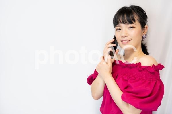 スマホで通話する女性(白背景)の写真