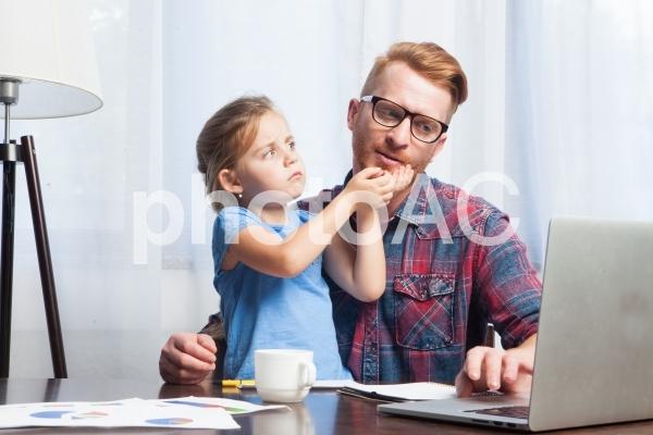 自宅で娘に邪魔されながら仕事するお父さんの写真