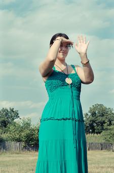 外国 海外 屋外 野外 自然 人物 1人 外国人 白人 セルビア人 大人 若い 女性 女 女の子 膝から上 ブルネット 黒髪 セミロング まとめ髪 ひっつめ髪 無造作ヘア 普段着 青緑の服 ワンピース ノースリーブ キャミソールワンピース ネックレス ペンダント レザーコード ブレスレット アクセサリー 眼鏡 メガネ めがね 植え込み 低木 木 木立 芝生 柵 微笑む 微笑 笑顔 手を振る 挨拶 あいさつ 陽射 まぶしい 隠す かざす 空 雲 mdff021