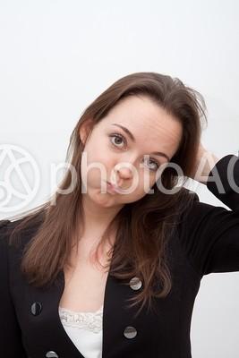 頭を触って口を膨らませる女性の写真