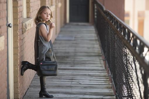 人物 こども 子供 女の子 少女  外国人 外人 キッズモデル かわいい 屋外 ポーズ 表情 ポートレイト ポートレート ファッション おしゃれ ワンピース モノトーン バッグ 外出 お出かけ 壁 れんが 煉瓦 片足立ち 待ち合わせ 待つ 全身 mdfk015