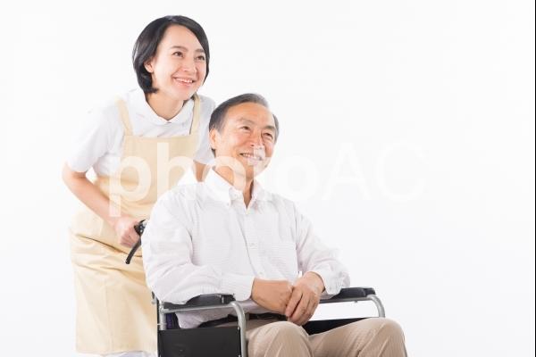 車椅子に乗った男性と看護師30の写真