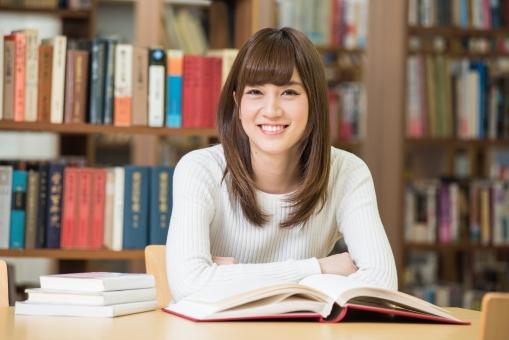 図書館で本を広げて座っている女子大生6の写真