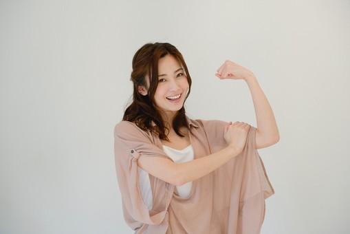 日本人 女性 女 30代 アラサー グレーバック 背景 グレー ポーズ ハーフアップ 髪型 茶髪 ナチュラル 私服 カジュアル ピンク ピンクベージュ 主婦 OL 力持ち 腕 腕力 体力 元気 健康 健康的 筋肉 筋トレ トレーニング 笑顔 スマイル 力こぶ 任せて おまかせ mdjf013