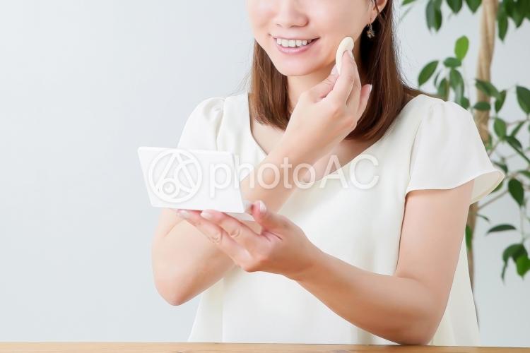 パフで化粧する女性の写真