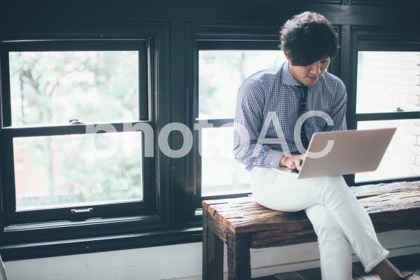ベンチでノートパソコンを使う会社員の男性6の写真