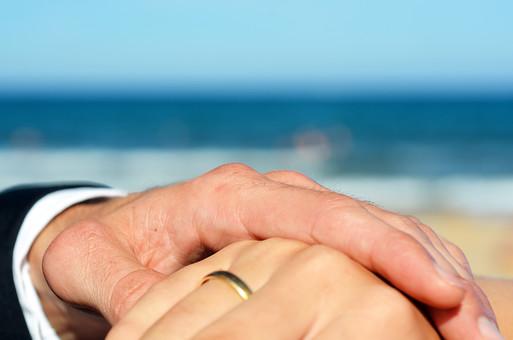 人物 外国人 新郎 新婦 花婿 花嫁 男性 女性 男の人 女の人 成人 男女 カップル 新婚 アベック 夫婦 夫 妻 ポーズ 手を取る 指輪 指輪の交換 マリッジリング 金 儀式 嵌める 手 指 幸せ 結婚式 屋外 室外 自然 海 空 青い グラデーション 晴天 天気 晴れ 青空 ぼやける ピンボケ 砂浜