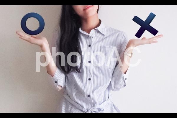 マルかバツを選ぶ女性の写真