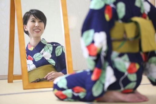 浴衣を着て鏡を見る女性の写真