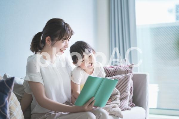 ソファに座って絵本を読む親子の写真