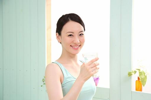 女性 若い女性 女 人物 部屋 一人暮らし リラックス 日本人 ライフスタイル 20代 休日 健康 美容 水 ミネラルウォーター コップ 飲む 水分補給 グラス 朝 上半身 笑顔 スマイル 屋内 室内 mdjf001