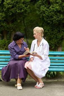 屋外 野外 外 病院 庭 公園 ベンチ 外国人 老人 高齢者 女性 おばあさん おばあちゃん 患者 女医 白人 金髪 白衣 医師 医者 スカート 座る 並ぶ 話す 会話 相談 聞く 聴診器 めがね メガネ 眼鏡 本 読む 見る 見せる mdff142 mdfs016