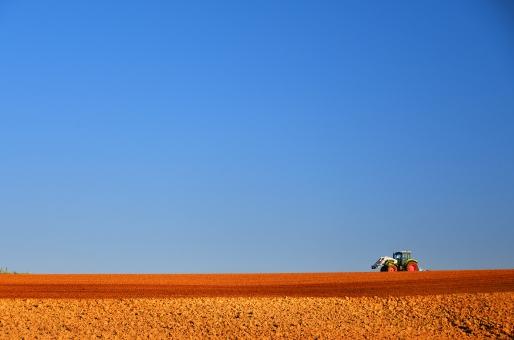 空と畑とトラクターの写真