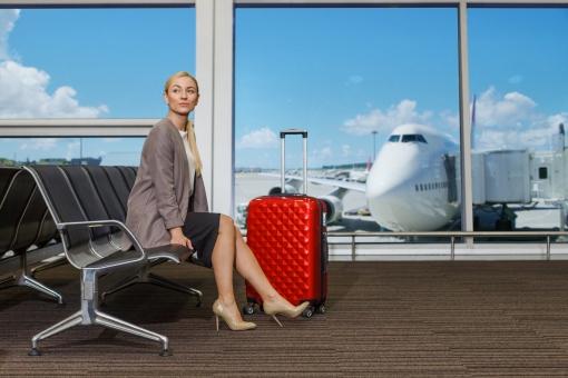 空港のベンチに座るビジネスウーマン1の写真