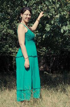 外国 海外 屋外 野外 自然 人物 1人 外国人 白人 セルビア人 大人 若い 女性 女 女の子 横向き ブルネット 黒髪 セミロング まとめ髪 ひっつめ髪 無造作ヘア 普段着 青緑の服 ワンピース ロングワンピース ノースリーブ キャミソールワンピース ネックレス ペンダント レザーコード ブレスレット 指輪 リング アクセサリー 眼鏡 メガネ めがね 低木 木 果樹 木の実 果実 木立 芝生 笑顔 微笑 微笑み 笑う mdff021
