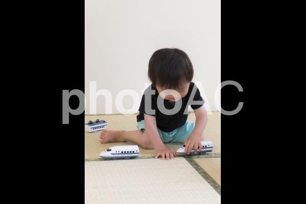 畳のヘリを線路に見立てて遊ぶ2歳児の写真