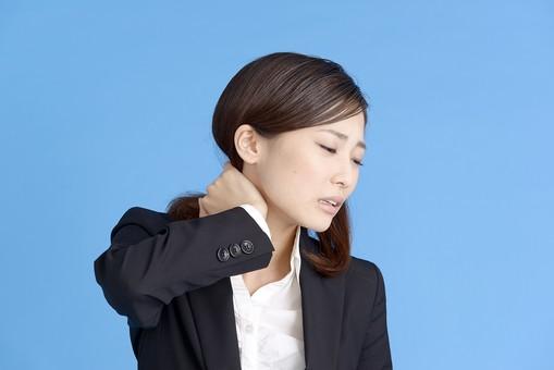 人物 女性 日本人 20代 若者  ビジネス スーツ 黒 紺色 セミロング  OL 社会人 会社員 ビジネスマン 就活  就職活動 真面目 ポーズ 屋内 スタジオ撮影  ブルーバック 上半身 首 頚椎 痛い 首に手をやる 疲れ 疲労 困った 凝り 肩凝り 肩こり mdjf013
