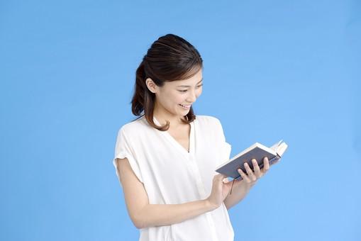 女性 ポーズ 人物 30代 日本人 黒髪 爽やか カジュアル 屋内 横向き 上半身 ブルーバック 青背景 半そで 白  本 見る 読む 持つ 両手 満足 楽しい ブルー 青 ブック 見つめる 読書 よく見る 感心 気がつく mdjf013