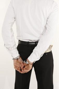 人物 男性 手 手錠 現金 お金 マネー お札 犯罪 犯罪者 犯人 逮捕 賄賂 ワイロ 贈収賄 不正行為 ポケット 後ろ姿 後姿 後ろ手 事件 詐欺 窃盗 盗み 泥棒 白バック 白背景 捕まる 容疑者 汚職