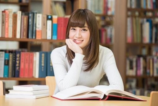 図書館で本を広げて座っている女子大生1の写真