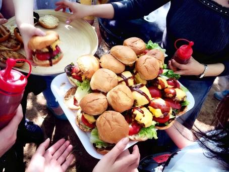 ハンバーガー BBQ 人 女性 男性 手 ソース ハンバーグ バンズ トマト チーズ レタス イベント バーベキュー 食べ物 食事 立食 パーティー グルメ 屋外 野外 アウトドア イベント 夏