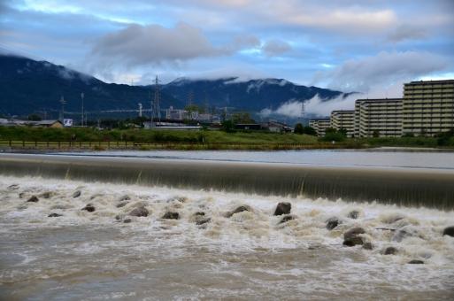 河川 川 濁流 豪雨 雨上がり 濁った 汚れた 流れ 勢い 水飛沫 荒々しい 危険 山 稜線 雲 マンション 建物 建築物 建造物 緑 土手 自然 景色 風景 関西 大阪