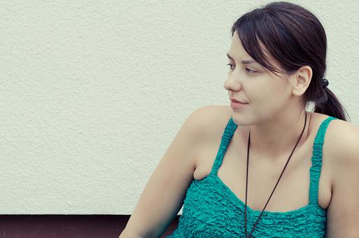 外国 海外 屋外 人物 1人 外国人 白人 セルビア人 大人 若い 女性 女 女の子 胸から上 ブルネット 黒髪 セミロング まとめ髪 ひっつめ髪 無造作ヘア 普段着 青緑の服 ノースリーブ キャミソール ネックレス ペンダント レザーコード アクセサリー 白壁 見つめる 考えごと 悩む mdff021